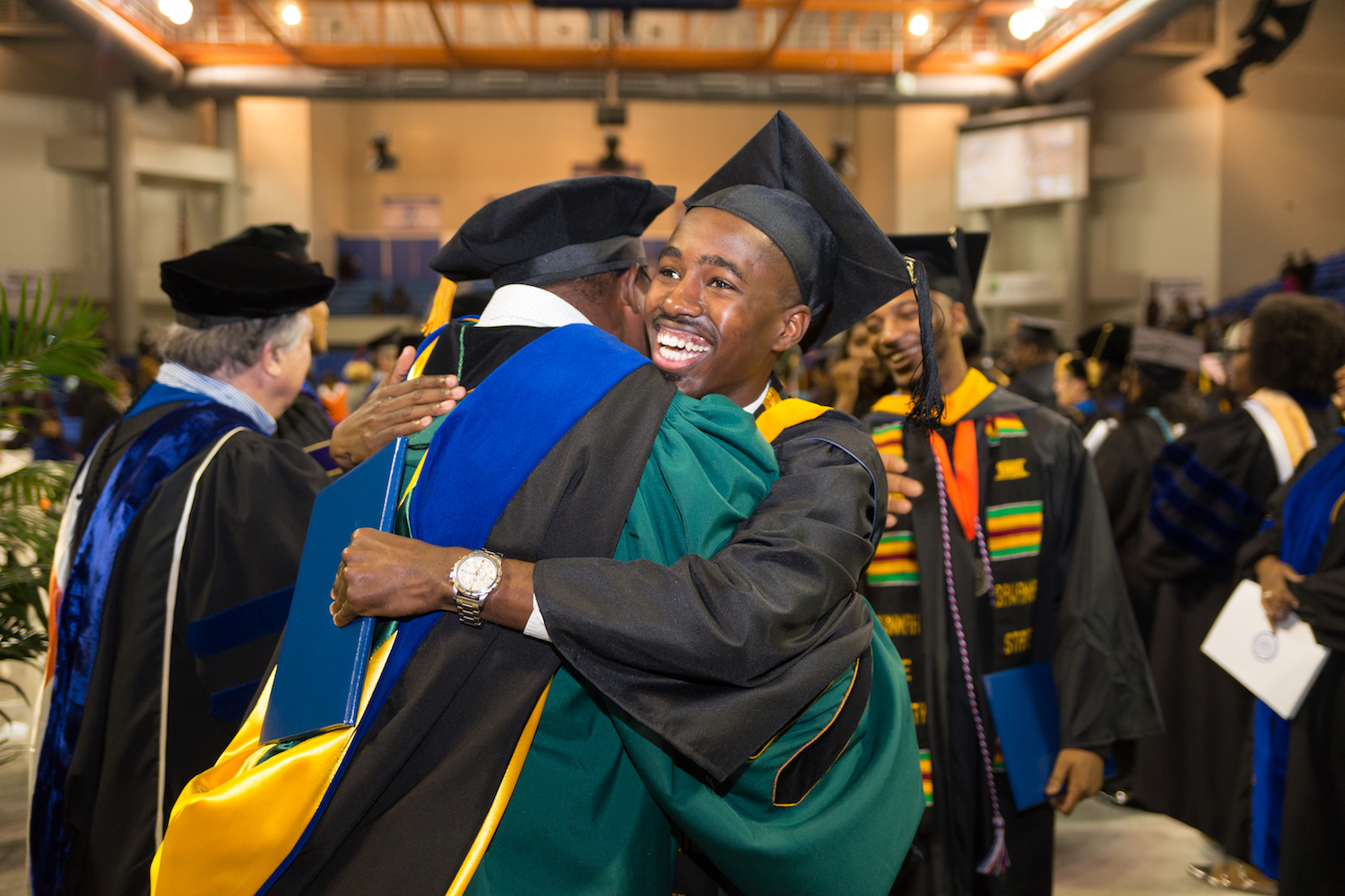 Graduating student hugs his professor