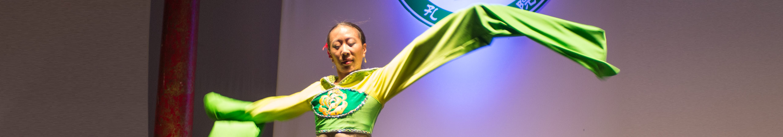 Asian dancer in colorful costume with yellow ribbon.
